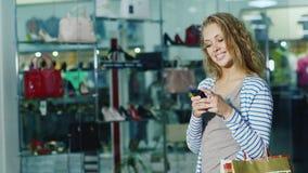 Ο ελκυστικός θηλυκός αγοραστής με τις τσάντες αγορών χρησιμοποιεί ένα smartphone Είναι απέναντι από το κατάστημα παπουτσιών προθη φιλμ μικρού μήκους