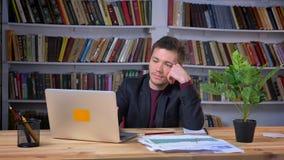 Ο ελκυστικός καυκάσιος επιχειρηματίας παίρνει ενοχλημένος becasuse του προβλήματος εργαζόμενος στο lap-top με μια οθόνη επαφής φιλμ μικρού μήκους