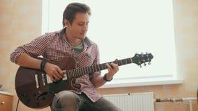 Ο ελκυστικός μουσικός νεαρών άνδρων συνθέτει τη μουσική στην κιθάρα και τα παιχνίδια, άλλο μουσικό όργανο στο πρώτο πλάνο απόθεμα βίντεο