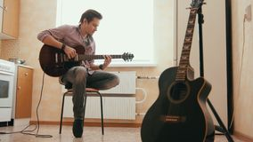Ο ελκυστικός μουσικός νεαρών άνδρων συνθέτει τη μουσική στην κιθάρα και παίζει στην κουζίνα, άλλο μουσικό όργανο απόθεμα βίντεο