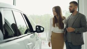 Ο ελκυστικός νέος βέβαιος γενειοφόρος τύπος ζευγών και η όμορφη φίλη του επιλέγουν το νέο αυτοκίνητο εξετάζοντας μαζί απόθεμα βίντεο