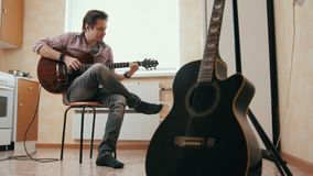 Ο ελκυστικός νέος μουσικός συνθέτει τη μουσική στην κιθάρα, άλλο μουσικό όργανο στο πρώτο πλάνο απόθεμα βίντεο