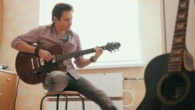Ο ελκυστικός νέος μουσικός συνθέτει τη μουσική στην κιθάρα και τα παιχνίδια, άλλο μουσικό όργανο στο πρώτο πλάνο απόθεμα βίντεο