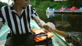 Ο ελκυστικός νέος τύπος brunette κάθεται σε μια βάρκα, χαμογελά και κωπηλατεί με τα κουπιά Ευτυχής νεαρός άνδρας σε ένα ριγωτό πο απόθεμα βίντεο