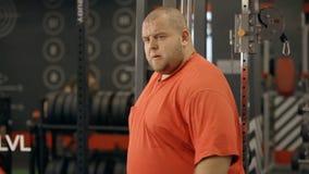 Ο ελκυστικός νεαρός άνδρας εξετάζει τον στην αθλητική γυμναστική απόθεμα βίντεο