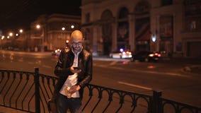Ο ελκυστικός νεαρός άνδρας περπατά μέσω της πόλης το βράδυ και πίνει τον καφέ φιλμ μικρού μήκους