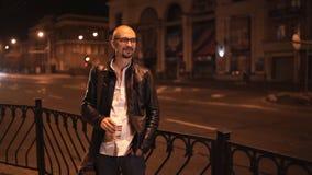 Ο ελκυστικός νεαρός άνδρας περπατά μέσω της πόλης το βράδυ και πίνει τον καφέ απόθεμα βίντεο