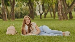 Ο ελκυστικός σπουδαστής νέων κοριτσιών με ένα smartphone βρίσκεται σε ένα πάρκο χλόης Υπόλοιπο κατά τη διάρκεια της μελέτης Στοκ Φωτογραφία