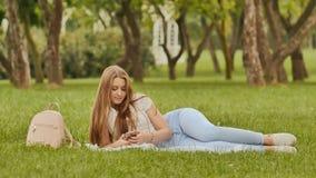 Ο ελκυστικός σπουδαστής νέων κοριτσιών με ένα smartphone βρίσκεται σε ένα πάρκο χλόης Υπόλοιπο κατά τη διάρκεια της μελέτης Στοκ Φωτογραφίες