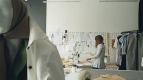 Ο ελκυστικός σχεδιαστής ιματισμού γυναικών εξετάζει τα σκίτσα ενδυμάτων που κρεμούν στον τοίχο επιλέγοντας έπειτα τα νέα σχέδια μ απόθεμα βίντεο
