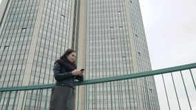 Ο ελκυστικός τουρίστας έντυσε στην περιστασιακή ένδυση χρησιμοποιώντας την εφαρμογή σε Smartphone για την πλοήγηση στην πόλη, στά Στοκ Φωτογραφίες