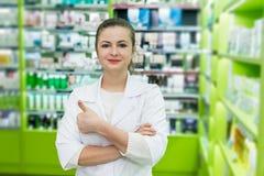 Ο ελκυστικός χαμογελώντας φαρμακοποιός γυναικών θέτει στο φαρμακείο στοκ εικόνες