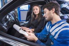 Ο εμπειρογνώμονας αυτοκινήτων παρουσιάζει επιδιορθώσεις στον πελάτη στοκ φωτογραφίες