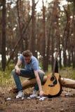 Ο εμπνευσμένος κιθαρίστας δημιουργεί την έννοια πεζοπορίας φύσης στοκ εικόνες