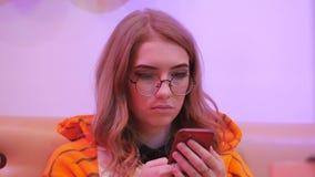 Ο εμψυχωτής νέων κοριτσιών έντυσε δεδομένου ότι μια συνεδρίαση τιγρών σε έναν καφέ χρησιμοποιεί ένα smartphone απόθεμα βίντεο