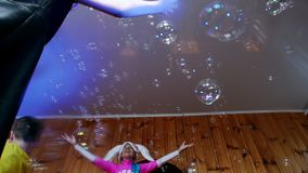 Ο εμψυχωτής τακτοποίησε μια επίδειξη των φυσαλίδων σαπουνιών για τα παιδιά Τα παιδιά πηδούν και χορεύουν κάτω από πολλές φυσαλίδε απόθεμα βίντεο