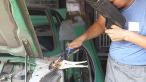 Ο ενήλικος επισκευαστής ή μηχανικό να κάνει εργαζομένων ενώνει στενά την εργασία με τη μηχανή συγκόλλησης και την προστατευτική μ απόθεμα βίντεο