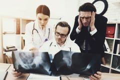 Ο ενήλικος επιχειρηματίας τρομάζεται από τη διάγνωση του γιατρού που κρατά την ακτηνογραφία στο ιατρικό γραφείο Στοκ Εικόνα
