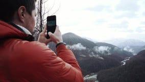 Ο ενήλικος τουρίστας στο χειμερινό σακάκι παίρνει τις εικόνες ενός όμορφου τοπίου βουνών απόθεμα βίντεο