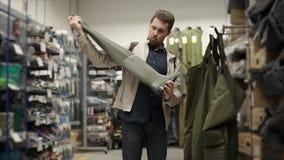 Ο ενήλικος ψαράς επιλέγει τις λαστιχένιες μπότες στα καταστήματα της αθλητικής ενδυμασίας απόθεμα βίντεο