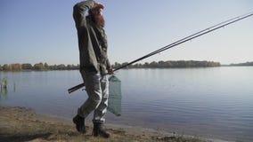 Ο ενήλικος ψαράς με τη μακριά γενειάδα περπατά κοντά στον ποταμό με την αλιεία των ράβδων και της στεφάνης ενέδρας καθαρών κίνηση απόθεμα βίντεο