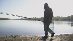 Ο ενήλικος ψαράς με τη μακριά γενειάδα περπατά κοντά στον ποταμό με την αλιεία των ράβδων και της στεφάνης ενέδρας καθαρών κίνηση φιλμ μικρού μήκους
