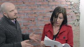 Ο ενήλικοι άνδρας και η γυναίκα συζητούν το χειρόγραφο σε χαρτί συγκινήσεις Τουβλότοιχος στο υπόβαθρο απόθεμα βίντεο