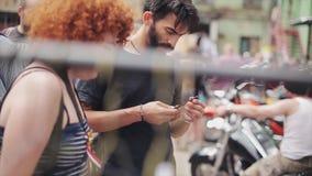 Ο ενήλικος γενειοφόρος άνδρας και η κοκκινωπή γυναίκα εξετάζουν τη χτένα στην έκθεση οδών αγοραστές θερινό ηλιόλουστο swallowtail φιλμ μικρού μήκους