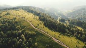 Ο εναέριος πυροβολισμός από τον πετώντας κηφήνα ενός νέου ζεύγους των τουριστών απολαμβάνει το όμορφο τοπίο βουνών στο ηλιοβασίλε φιλμ μικρού μήκους