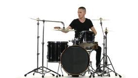 Ο ενεργητικός επαγγελματικός μουσικός παίζει την καλή μουσική στα τύμπανα Άσπρη ανασκόπηση απόθεμα βίντεο
