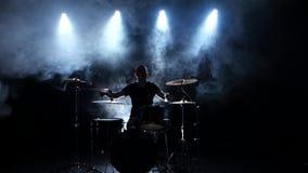 Ο ενεργητικός μουσικός παίζει την καλή μουσική στα τύμπανα Μαύρο καπνώές υπόβαθρο πίσω φως σκιαγραφία απόθεμα βίντεο