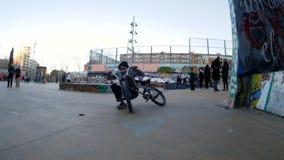 Ο ενεργός αναβάτης BMX κάνει τις διαφορετικά περιστροφές και τα τεχνάσματα στο ποδήλατο στο αστικό περιβάλλον φιλμ μικρού μήκους