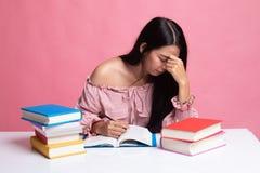 Ο εξαντλημένος ασιατικός αποκτημένος γυναίκα πονοκέφαλος διάβασε ένα βιβλίο με τα βιβλία στον πίνακα στοκ εικόνα με δικαίωμα ελεύθερης χρήσης