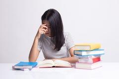 Ο εξαντλημένος ασιατικός αποκτημένος γυναίκα πονοκέφαλος διάβασε ένα βιβλίο με τα βιβλία στον πίνακα στοκ εικόνες
