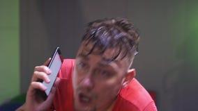 Ο εξαντλημένος καυκάσιος γενειοφόρος τύπος ιδρώτα κάνει καρδιο και την ομιλία στο τηλέφωνο απόθεμα βίντεο
