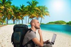 Ο εξερευνητής προγραμματίζει ένα νέο ταξίδι σε μια τροπική παραλία με το lap-top του Στοκ Εικόνες