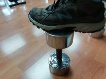 Ο εξοπλισμός γυμναστικής έχει τον αλτήρα, μερικά παπούτσια που τίθεντ στοκ εικόνα