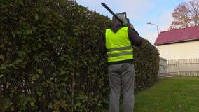 Ο εξωραΐζοντας εργαζόμενος παίρνει τις εικόνες του φράκτη θάμνων φιλμ μικρού μήκους