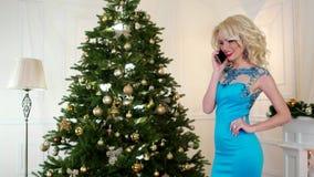 Ο εορτασμός Χριστουγέννων, όμορφο κορίτσι στο φόρεμα διακοπών μιλά σε ένα κινητό τηλέφωνο, επιθυμεί μια καλή χρονιά απόθεμα βίντεο