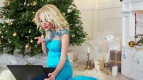 Ο εορτασμός Χριστουγέννων, όμορφο κορίτσι στο φόρεμα διακοπών μιλά στις τηλεοπτικές κλήσεις, μέσω του lap-top, επιθυμεί μια καλή  απόθεμα βίντεο