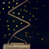 Ο εορταστικός χρυσός συμπλέκτης βραδιού με το αστέρι ψεκάζει στο Μαύρο Holi Στοκ φωτογραφία με δικαίωμα ελεύθερης χρήσης