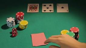 Ο επαγγελματίας πόκερ που ελέγχει τις κάρτες, στοιχημάτιση πελεκά για να αυξήσει την τράπεζα, στρατηγική παιχνιδιών απόθεμα βίντεο