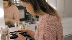 Ο επαγγελματικοί καλλιτέχνης και το hairstylist makeup δημιουργούν μια όμορφη εικόνα για ένα όμορφο νέο κορίτσι φιλμ μικρού μήκους
