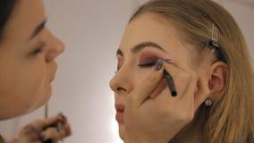 Ο επαγγελματικοί καλλιτέχνης και το hairstylist makeup δημιουργούν μια όμορφη εικόνα για ένα όμορφο νέο κορίτσι απόθεμα βίντεο