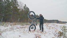 Ο επαγγελματικός ακραίος ποδηλάτης αθλητικών τύπων ανυψώνει ένα παχύ ποδήλατο σε υπαίθριο Ο ποδηλάτης κρατά στο δασικό περίπατο α φιλμ μικρού μήκους