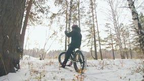 Ο επαγγελματικός ακραίος ποδηλάτης αθλητικών τύπων κάθεται ένα παχύ ποδήλατο σε υπαίθριο Ο ποδηλάτης ξαπλώνει στο δασικό περίπατο απόθεμα βίντεο
