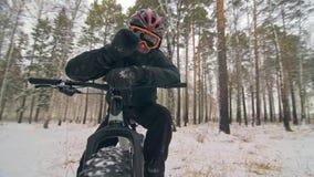 Ο επαγγελματικός ακραίος ποδηλάτης αθλητικών τύπων κάθεται ένα παχύ ποδήλατο σε υπαίθριο Ο ποδηλάτης ξαπλώνει στο δασικό περίπατο φιλμ μικρού μήκους