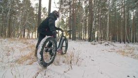 Ο επαγγελματικός ακραίος ποδηλάτης αθλητικών τύπων στέκεται ένα παχύ ποδήλατο σε υπαίθριο Ο ποδηλάτης ξαπλώνει στο δασικό περίπατ φιλμ μικρού μήκους