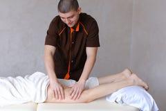 Ο επαγγελματικός αρσενικός μασέρ ζυμώνει τα πόδια του κοριτσιού στον ασθενή, ο οποίος λι Στοκ εικόνα με δικαίωμα ελεύθερης χρήσης
