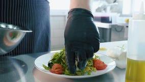 Ο επαγγελματικός αρχιμάγειρας βάζει τη σαλάτα στο πιάτο με το χέρι από το κύπελλο χάλυβα απόθεμα βίντεο